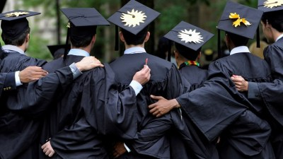 Students in graduation robes embracing with their backs to the camera.