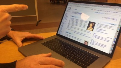 Three hands pointing at a computer screen on which a page from Wikipedia is showing.
