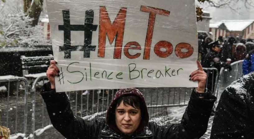Woman holding up a sign outdoors in the snow.