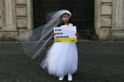 "A child actress dressed as a child bride and holding a sign that says ""Stop child marriage""."