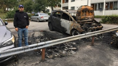 Hasan Tümtürk stands in front of his and other cars damaged by fire at a parking lot.