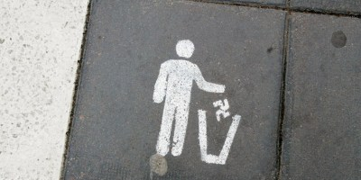 An image printed on the ground showing a stick man throwing a swastika into a bin..
