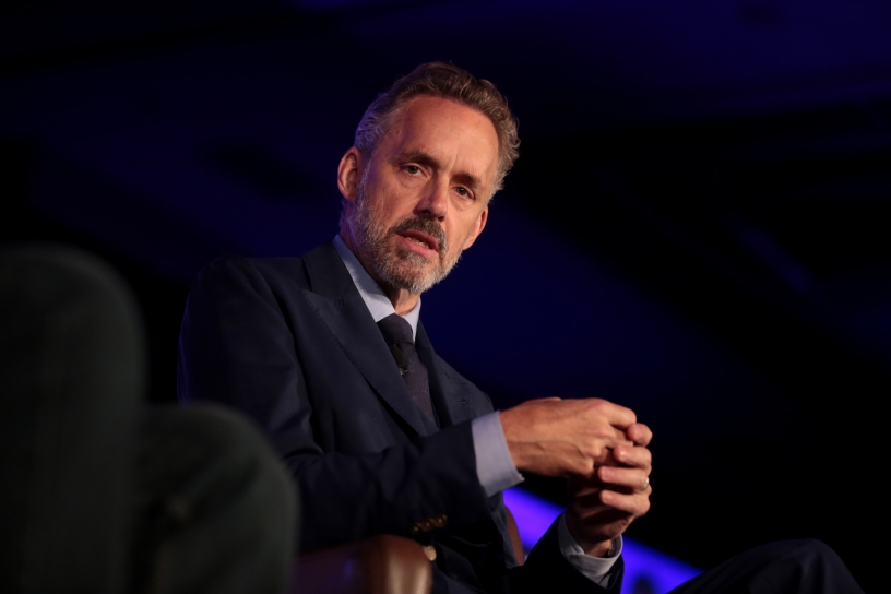Clinical psychologist Jordan Peterson sitting in an armchair. Photo taken from below.