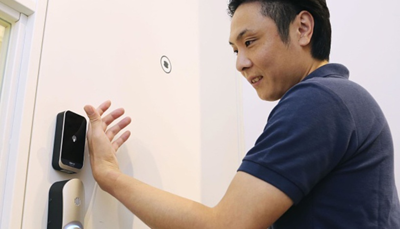 Man opens a door with the help of a microchip implanted in his hand.