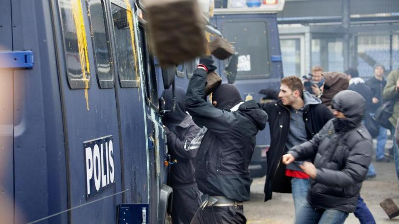 Rioters attack a police picket truck in Malmö, Sweden.