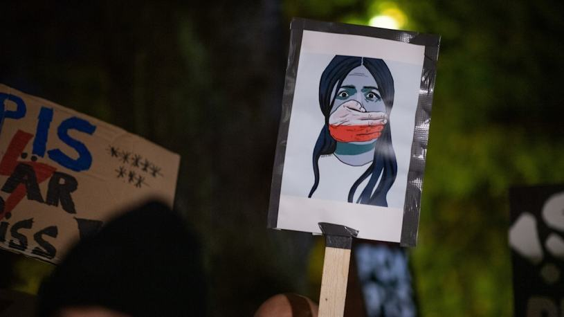 A plaque is held up during a protest outside the Polish embassy in Stockholm, Sweden.