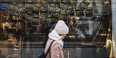 A woman dressed in a coat, scarf and hat walks past a shop where a sale is on.